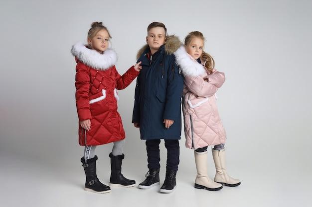 Herbstkollektion von kleidern für kinder und jugendliche. jacken und mäntel für herbstkaltes wetter. kinder posieren auf einem weißen hintergrund Premium Fotos