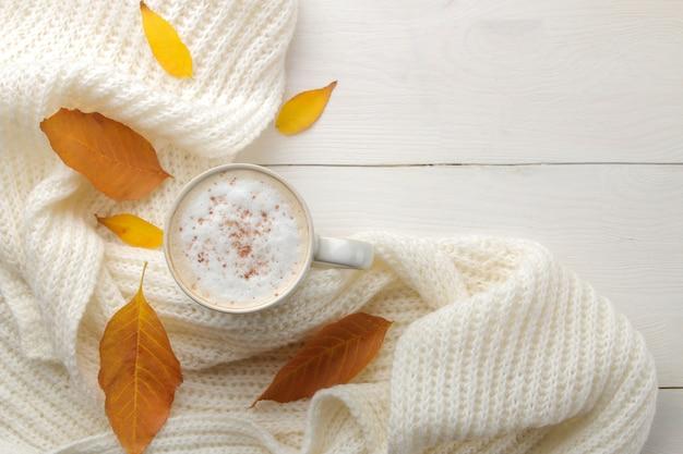 Herbstkomposition mit heißem kaffee, einem warmen schal und gelben blättern auf einem weißen holztisch. draufsicht mit platz für inschrift Premium Fotos