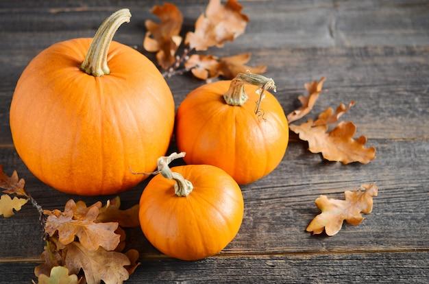 Herbstkonzept mit kürbisen auf einem rustikalen holztisch Premium Fotos