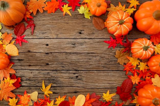 Herbstlaub auf hölzernem hintergrund Premium Fotos