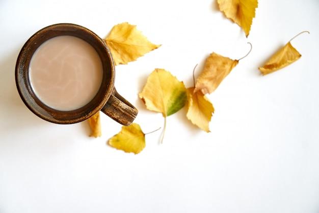 Herbstlaub mit kaffee- oder teeschale auf weiß Premium Fotos