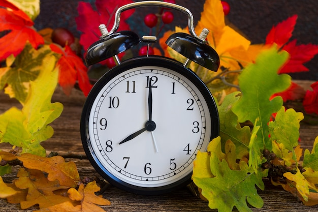 Herbstlaub mit wecker auf dem tisch Premium Fotos