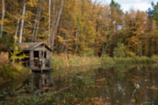 Herbstliche ländliche landschaft - herbst eichen in der nähe des teiches und einsames kleines haus Premium Fotos