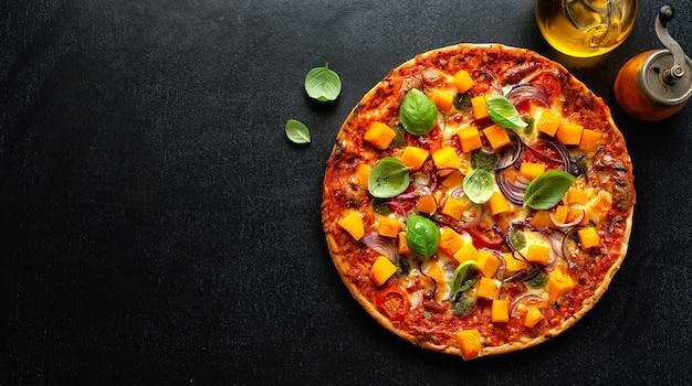 Herbstliche vegetarische pizza mit kürbis und gemüse auf dunklem hintergrund. banner Premium Fotos