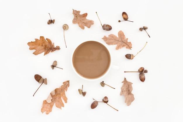 Herbstliches blasses muster, blätter, eicheln und tasse kaffee auf weiß Premium Fotos