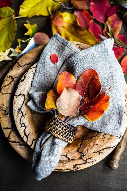 Herbstliches gedeck mit gelben und roten blättern auf rustikalem hintergrund mit kopienraum Premium Fotos