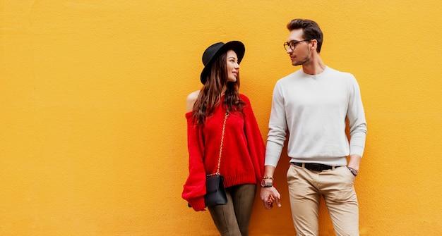 Herbstmodebild des eleganten stilvollen paares in der liebe, die hände hält und einander mit vergnügen ansieht. langhaarige frau im roten strickpullover mit ihrem freund posiert Kostenlose Fotos