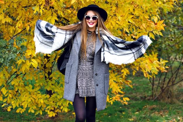 Herbstmodeporträt des atemberaubenden eleganten modells, das im park aufwirft, goldene blätter und kühles wetter, luxuriöse streetstyle-kleidung, helles make-up, großer schal, minikleid-überzugmantel und vintage-hut. Kostenlose Fotos
