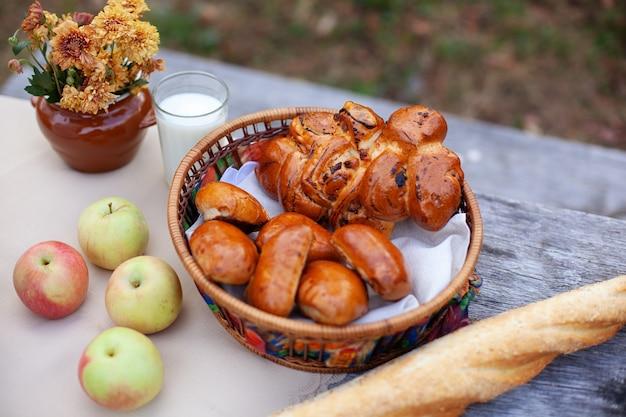 Herbstpicknick im freien mit brot, brötchen, äpfeln und blumenstrauß auf holztisch Premium Fotos