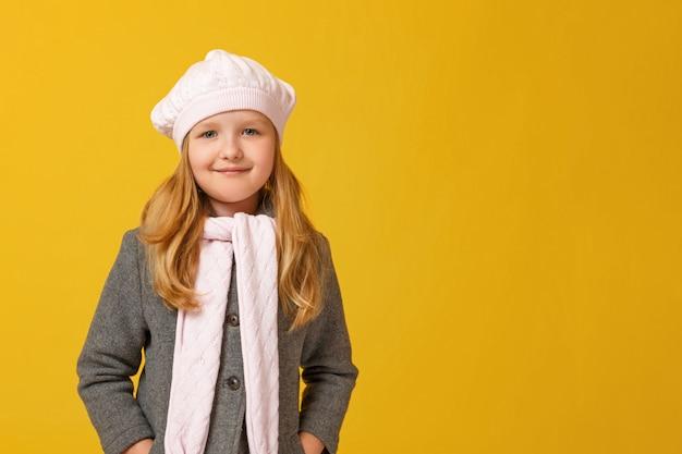 Herbstporträt eines kleinen mädchens in einem grauen mantel und in einem barett. Premium Fotos