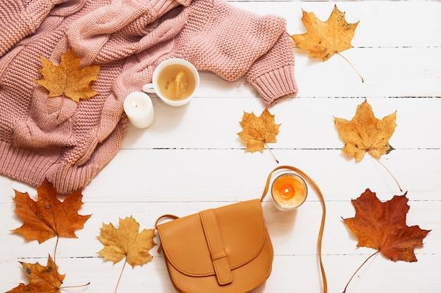 Herbststillleben, gelbe blätter, kürbis, kerzen, gestrickter pullover auf einer weißen draufsicht. Premium Fotos