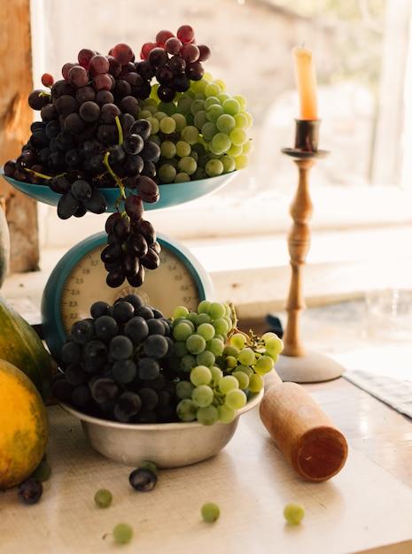 Herbststillleben mit kürbissen und trauben in einer metallschale, trauben auf einem weißen holztisch verteilt. im hintergrund ist eine kerze in einem kerzenhalter. herbsterntekonzept. Premium Fotos