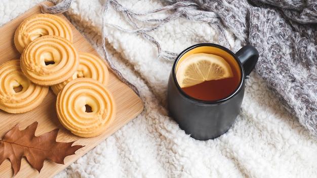 Herbststillleben mit tasse tee, plätzchen, strickjacke und blättern auf einer warmen weichen decke. Premium Fotos