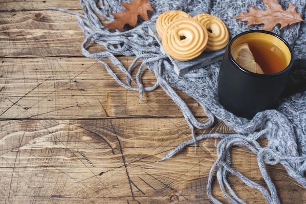 Herbststillleben mit tasse tee, plätzchen, strickjacke und blättern auf holzoberfläche. Premium Fotos