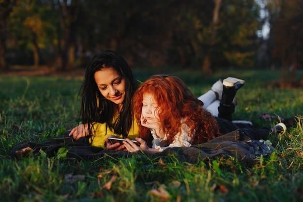 Herbststimmung, familienportrait. bezaubernde mutter und ihre rote haartochter haben spaß beim sitzen auf dem gefallenen Kostenlose Fotos