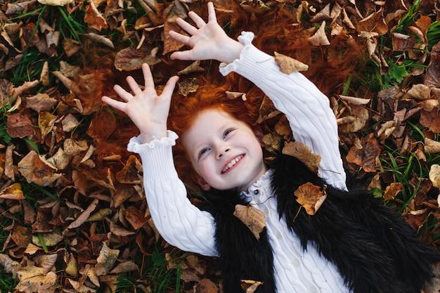 Herbststimmung, kinderportrait. kleines mädchen des reizend und roten haares schaut glücklich, auf dem gefallenen leav liegend Kostenlose Fotos