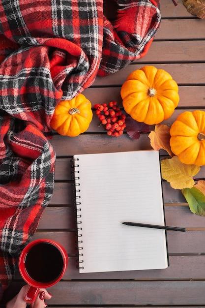 Herbststimmungskomposition auf einem holztisch mit kürbis eberesche und blättern. öffnen sie den notizblock und den schwarzen kaffee in der roten tasse und auf dem grauen holztisch Premium Fotos