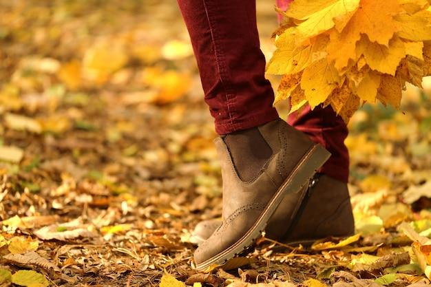 Herbstzeit. weibliche beine in den braunen velourslederstiefeln auf gelbe blätter. modische herbstschuhe Premium Fotos