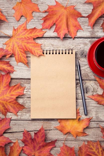 Herbstzusammensetzung mit arbeitsplatz mit leerem notizbuch, bleistift, roter tasse kaffee Premium Fotos