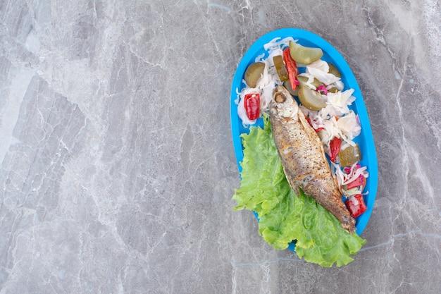 Hering und eingelegtes gemüse auf blauem teller. Kostenlose Fotos