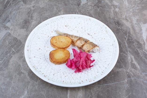 Heringsröllchen, kartoffel und rotkohl auf weißem teller. Kostenlose Fotos