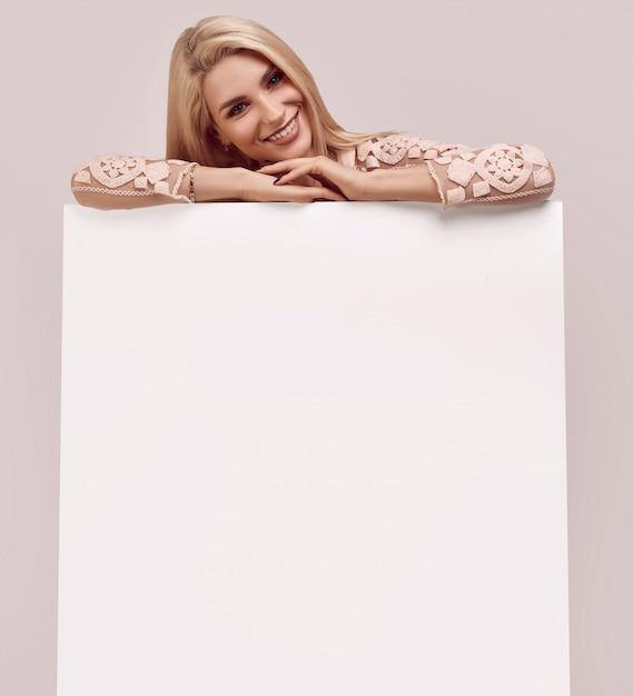 Herrliche blonde frau, die eine unbelegte anschlagtafel anhält Premium Fotos