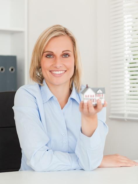 Herrliche blonde geschäftsfrau, die das miniaturhaus untersucht kamera zeigt Premium Fotos
