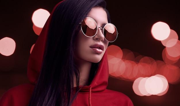 Herrliche brunettefrau im roten hoodie und in den gläsern auf nachtstadthintergrund Premium Fotos