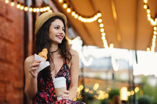 Herrliche brunettefrau mit tragendem sommerhut und -kleid des angenehmen auftrittes, die hörnchen hält Premium Fotos