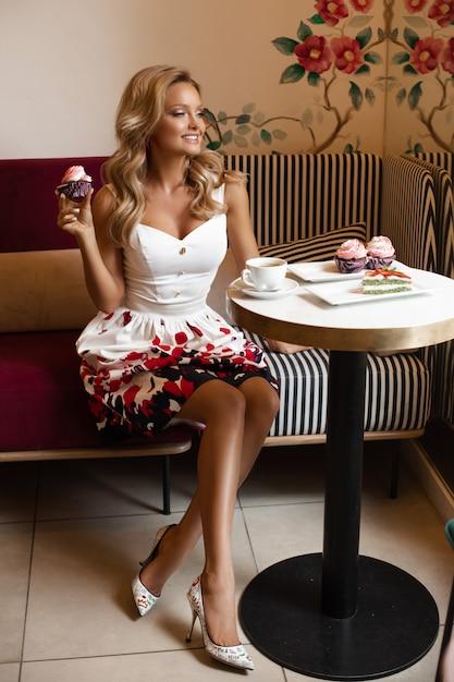 Herrliche dame in sommerkleidertrinkendem kaffee im café. Premium Fotos
