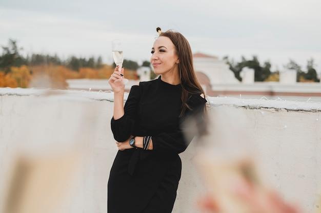 Herrliche frau im schwarzen kleid auf dem hintergrund von unscharfen champagnergläsern Kostenlose Fotos