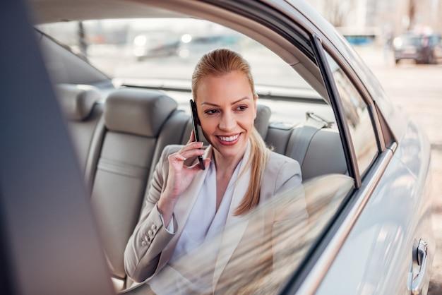 Herrliche geschäftsfrau, die smartphone im auto verwendet. Premium Fotos