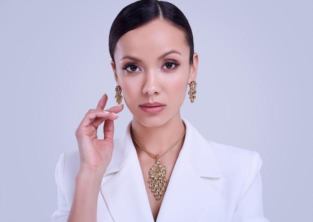 Herrlicher lateinischer weißer anzug der frauen in mode, der teuren schmuck trägt Premium Fotos