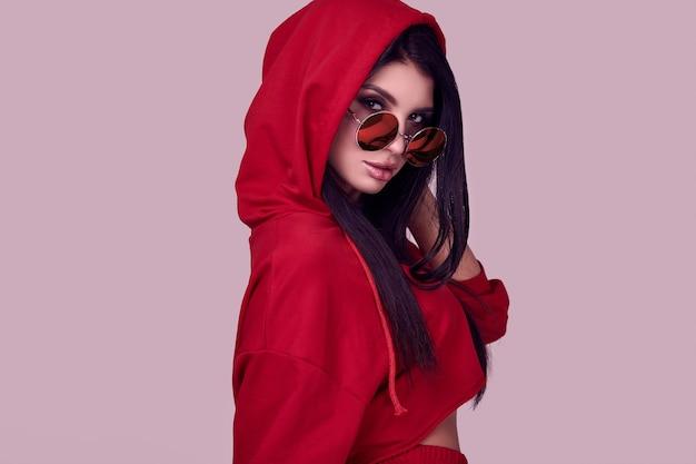Herrlicher roter hoodie der brunettefrau in mode im studio Premium Fotos