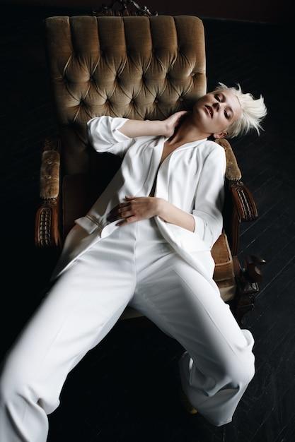 Herrliches blondes mode-modell sitzt im weißen anzug auf einem weichen lehnsessel Kostenlose Fotos
