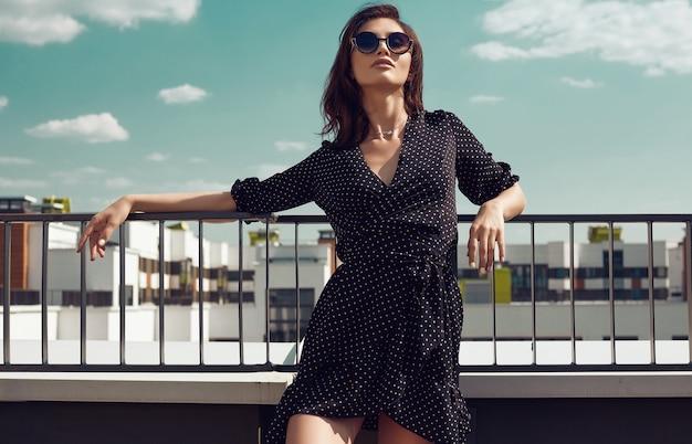 Herrliches helles kleid der brunettefrau in mode, das auf dem dach eines gebäudes aufwirft Premium Fotos