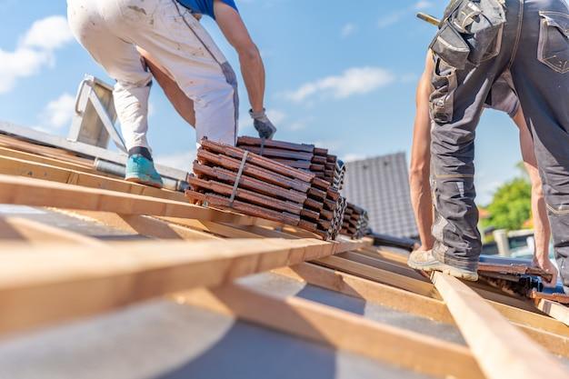 Herstellung von dächern aus keramikziegeln auf einem familienhaus Premium Fotos