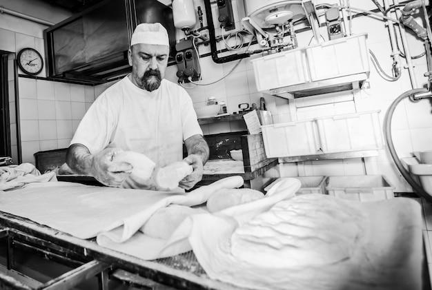 Herstellung von gebackenem brot mit einem holzofen in einer bäckerei Premium Fotos