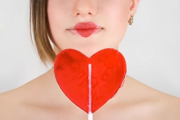 Herz auf den lippen der hübschen frauennahaufnahme mit herzlutscher Premium Fotos