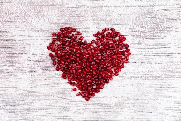 Herz formte draufsicht des granatapfels über weiße d-tabelle Kostenlose Fotos