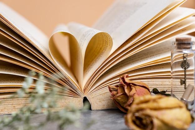 Herz geformt von der alten buchseite mit trockenen braunen rosen im weinlesefarbton Premium Fotos