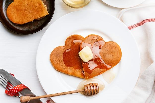 Herzförmige pfannkuchen auf hellem hintergrund. das konzept eines festlichen frühstücks zum valentinstag oder einer angenehmen überraschung für einen geliebten menschen Premium Fotos