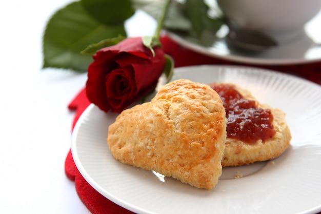 Herzförmige scones mit erdbeermarmelade und einer tasse tee Premium Fotos