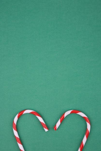 Herzförmige zuckerrohrsüßigkeit auf grünem hintergrund Premium Fotos