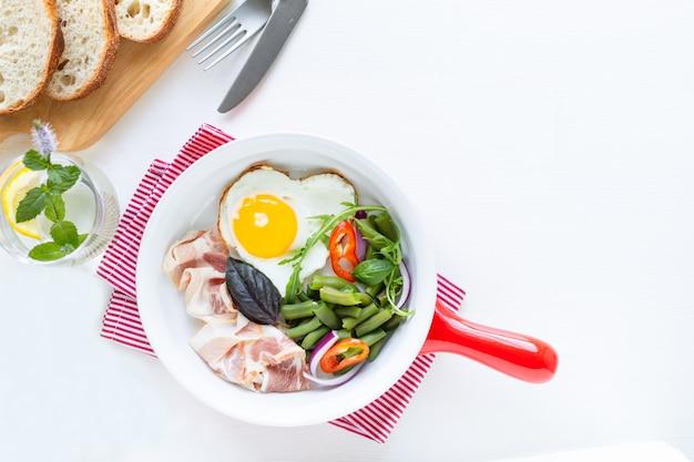 Herzförmiges ei, speck, grüne bohnen auf einer saucenpfanne, brot auf schneidebrett und wasser mit zitrone Kostenlose Fotos