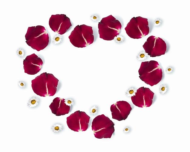 Herzformrahmen aus rosenblättern und gänseblümchenblumen mit kopierraum, valentinstag, flache lage Premium Fotos
