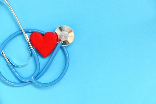 Herzgesundheit und rotes herz mit stethoskop auf blauer wand - weltherztag weltgesundheitstag oder welthypertonietag und krankenversicherungskonzept Premium Fotos