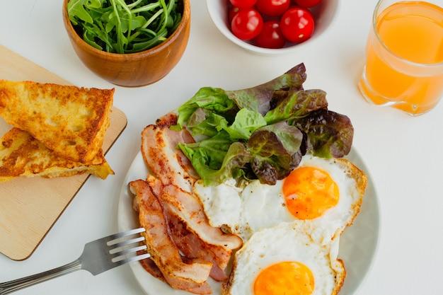 Herzhaftes frühstück. spiegeleier, speck, salat, kirschtomaten und toast. ansicht von oben Premium Fotos