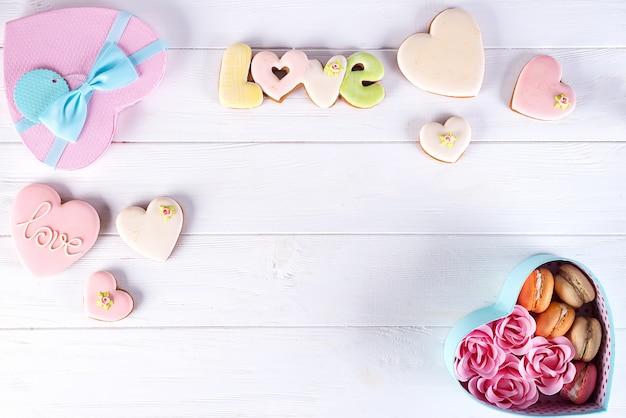 Herzkasten mit macarons und rose auf weißem hölzernem hintergrund, valentinstag Premium Fotos