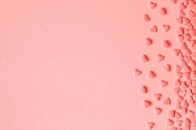 Herzsüßigkeiten besprüht sich gelegen auf der rechten seite auf rosa hintergrund in der koralle getont. Premium Fotos